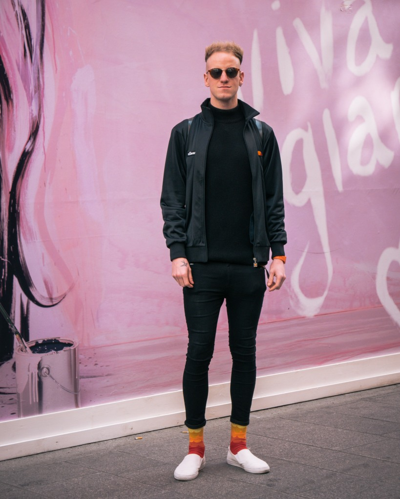 Man with sunglasses and bright socks against a pink wall