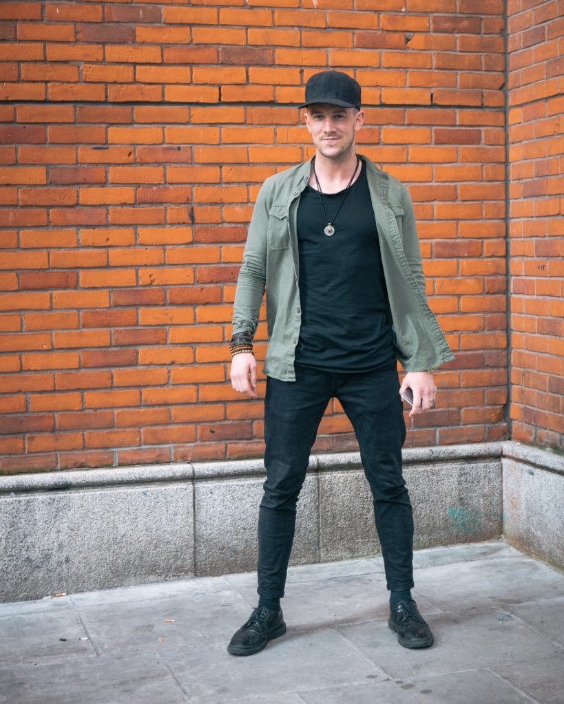 Stylish man in black in front of red brick wall in Dublin