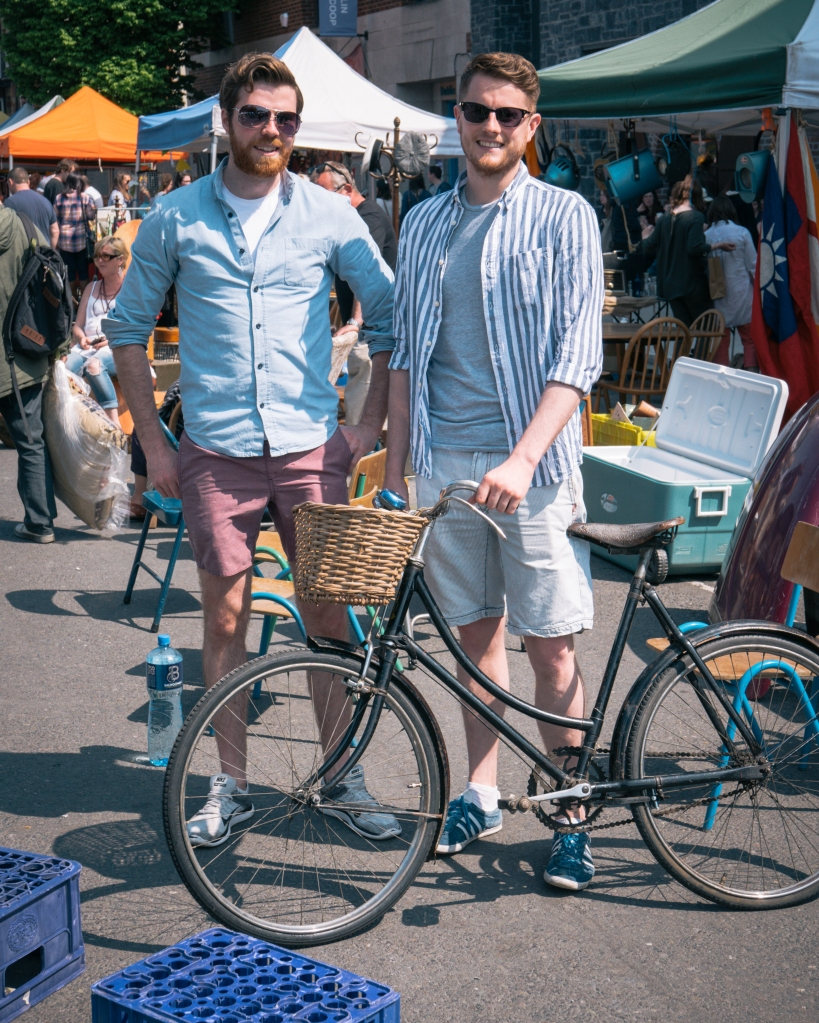 Two men at a fair in Dublin with a bike